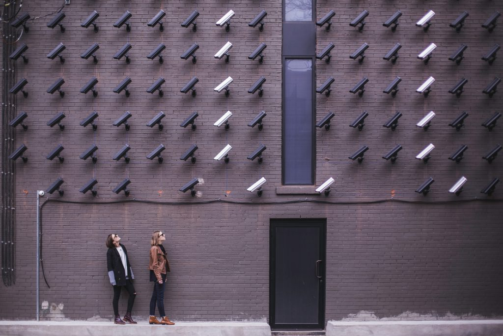 Imagem mostra duas mulheres em frente à uma parede de tijolos à vista repleta de câmeras de segurança, todas apontadas para a direção delas