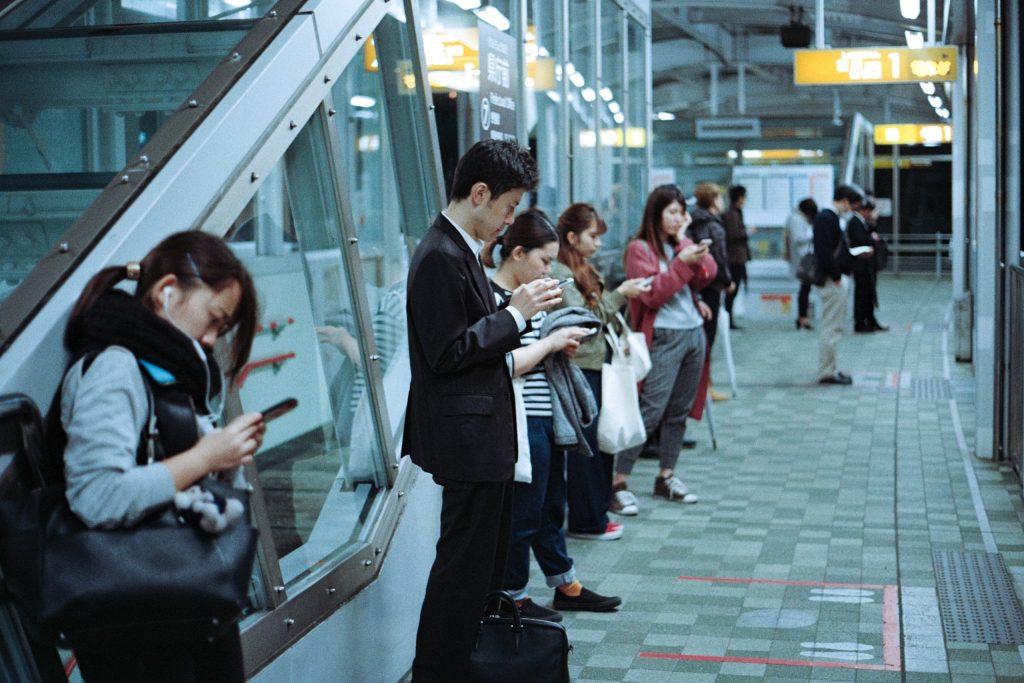Pessoas na estação do metrô usando o celular.