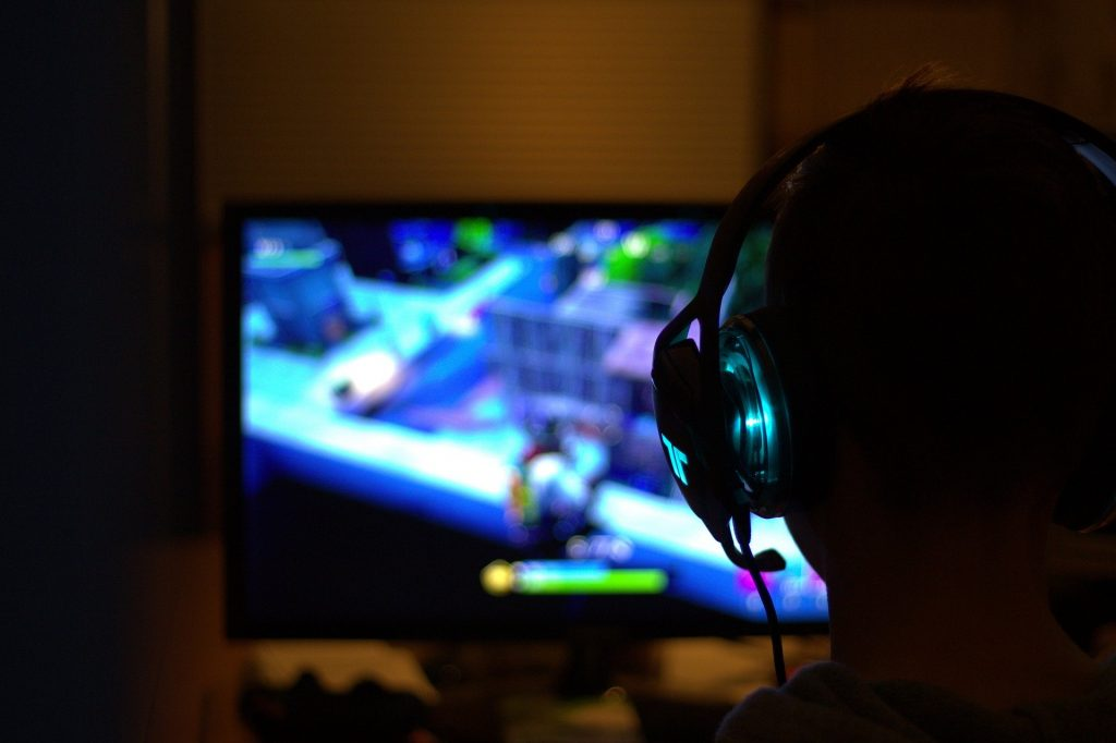Imagem mostra um homem jogando vídeo-game com um fone de ouvido.