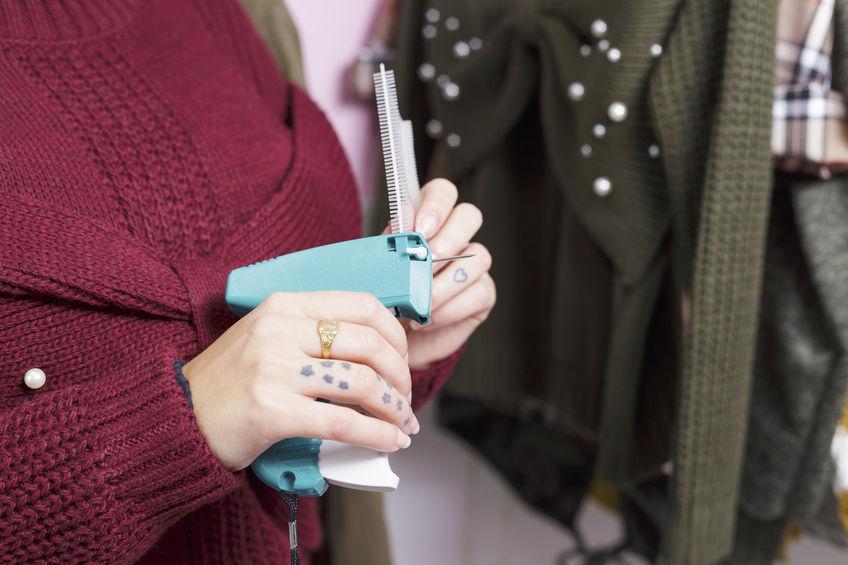 Imagem de mulher usando um rotulador azul para etiquetar roupas