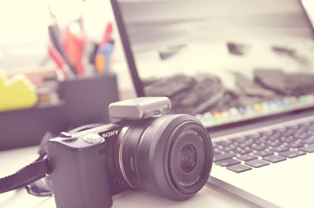 Na foto uma câmera digital ao lado de um notebook aberto em cima de uma mesa.