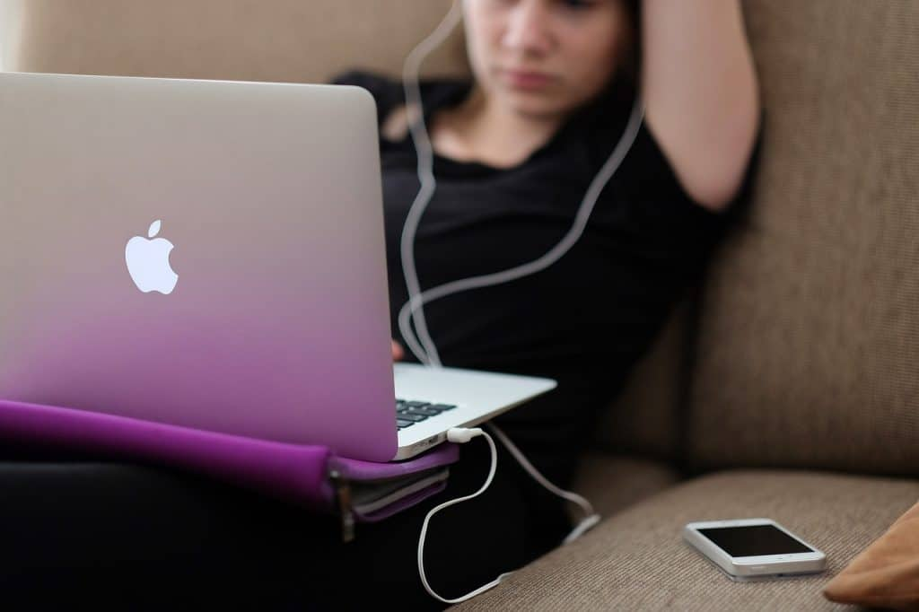 Uma mulher vestida de preto sentada em um sofá de forma confortável. Em cima dela existe uma capa para Macbook vazia. Acima da capa está o Macbook. No sofá também há um Iphone.