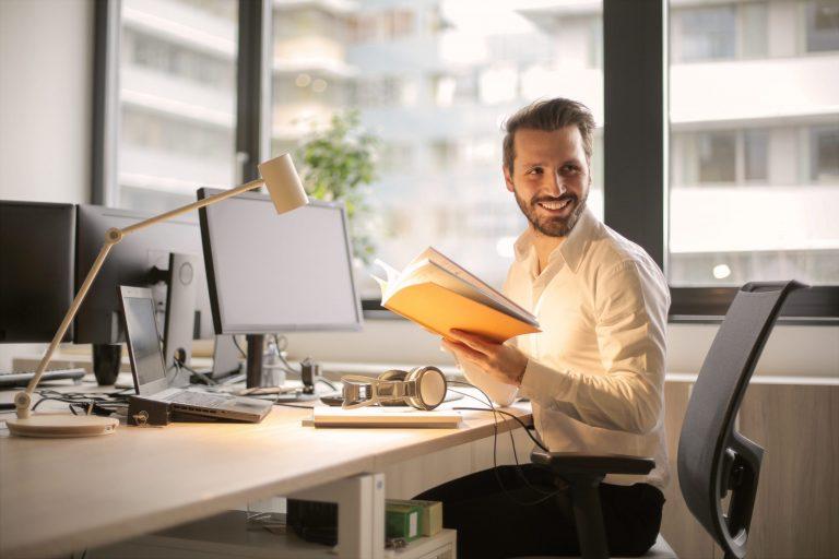 Imagem mostra um homem lendo um livro em frente a uma mesa com computador.