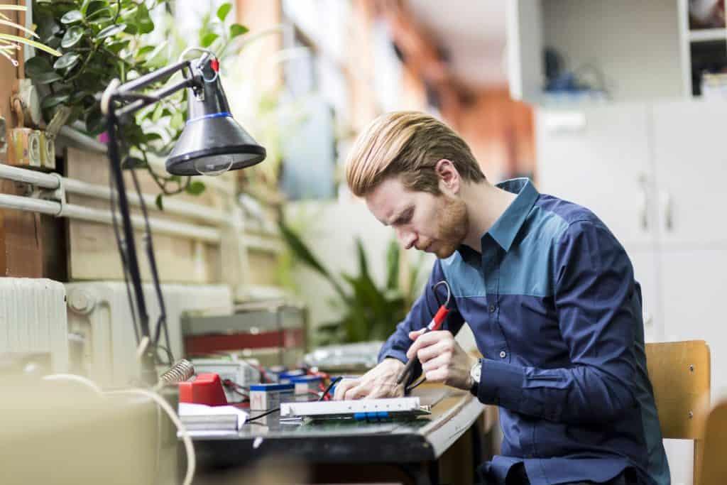 Na foto um homem soldando uma placa eletrônica, sentado em uma mesa.