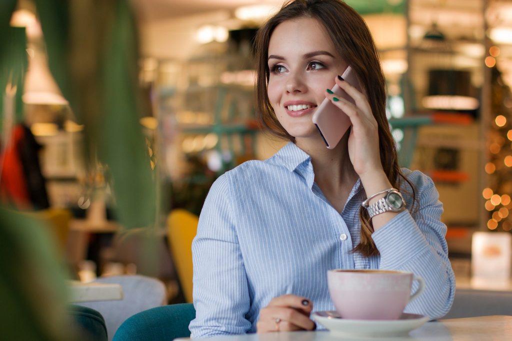 Imagem mostra uma mulher falando ao celular em um café.