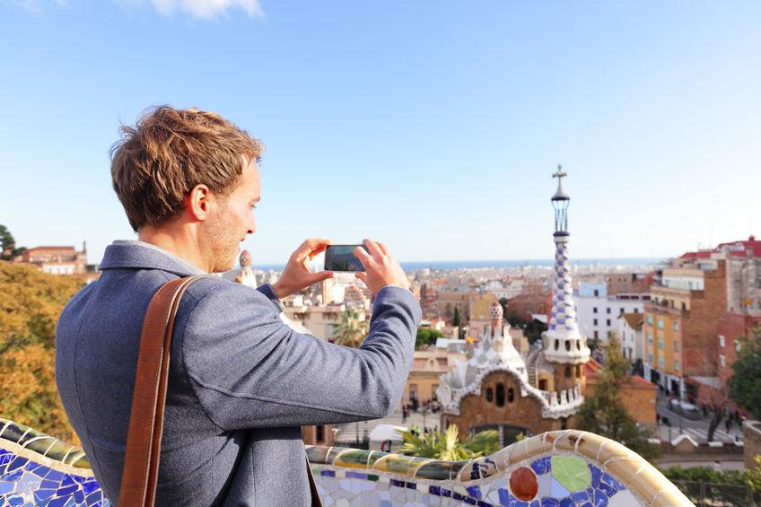 Homem fotografando com um celular do parque Guell, em Barcelona, na Espanha.