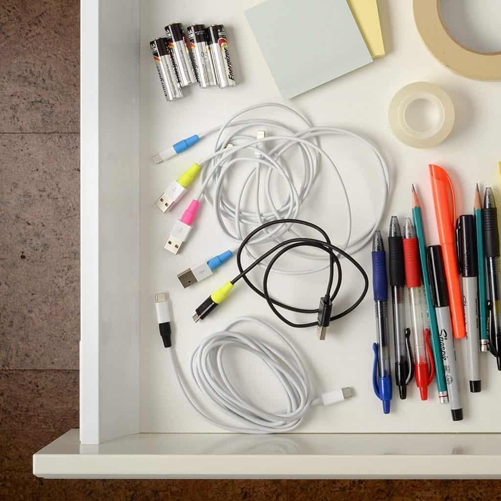 Gaveta repleta de cabos com protetores coloridos ao lado de outros materiais de escritório.