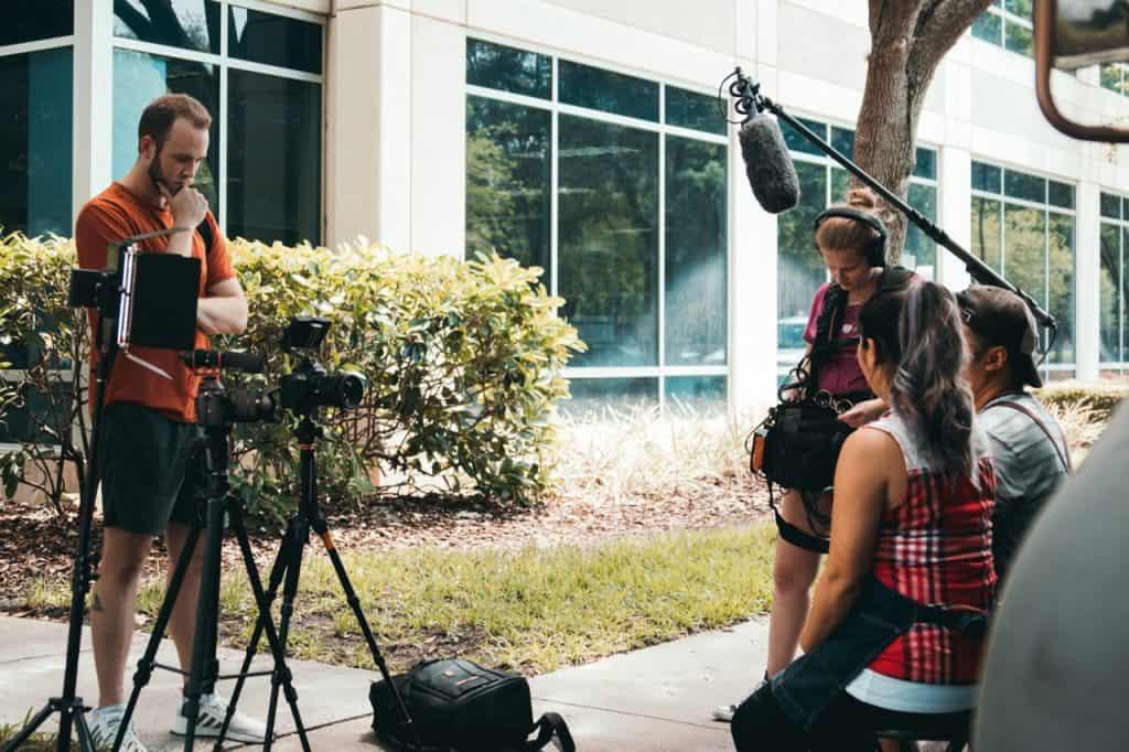 Imagem mostra uma gravação audiovisual com todo o aparato de câmera, captação de áudio, atores e diretor.