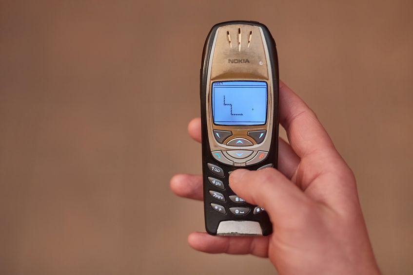 Mão jogando jogo da cobrinha em um Nokia.