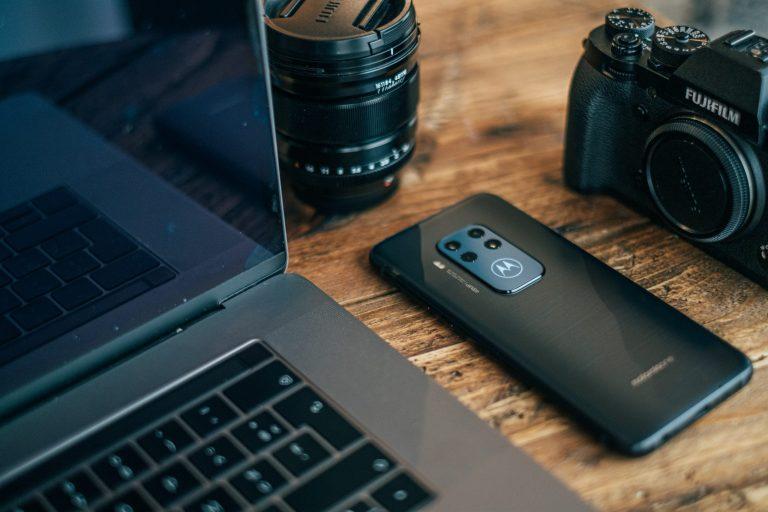 Notebook, smartphone Motorola e câmera fotográfica, todos sobre mesa.