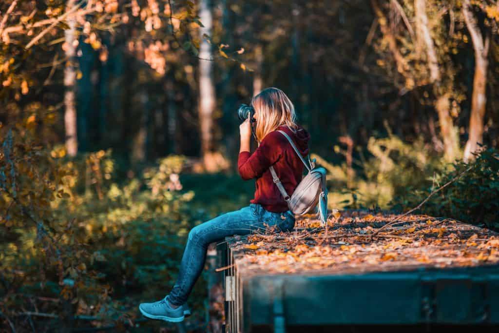 Na foto uma mulher sentada no meio de uma floresta tirando fotos.
