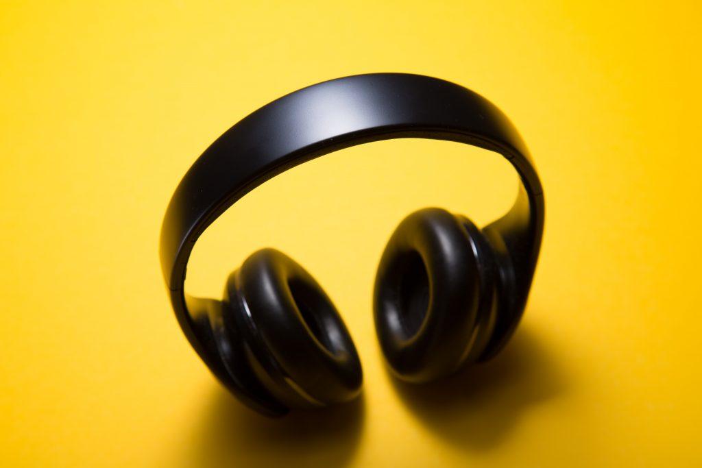 Imagem mostra um headphone sem fio sobre um fundo amarelo e limpo.