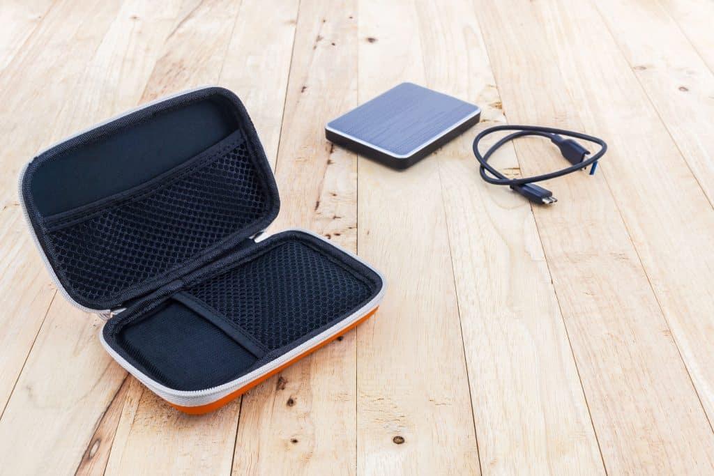 Imagem mostra um case de HD externo aberto vazio com o HD ao lado sobre superfície de madeira.