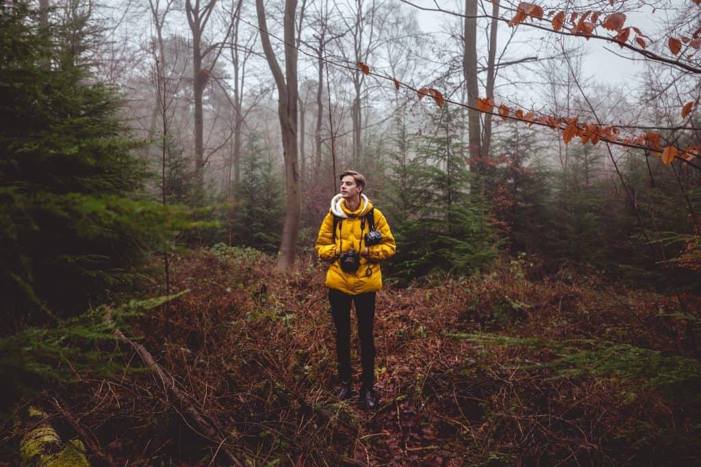 Imagem mostra um fotógrafo caminhando com uma mochila na floresta.