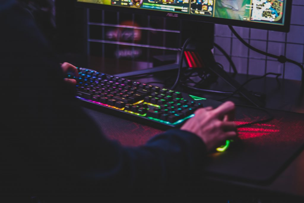 Imagem mostra a mão de uma pessoa usando um mouse, um teclado e um mouse pad gamer, enquanto joga um MMORPG.