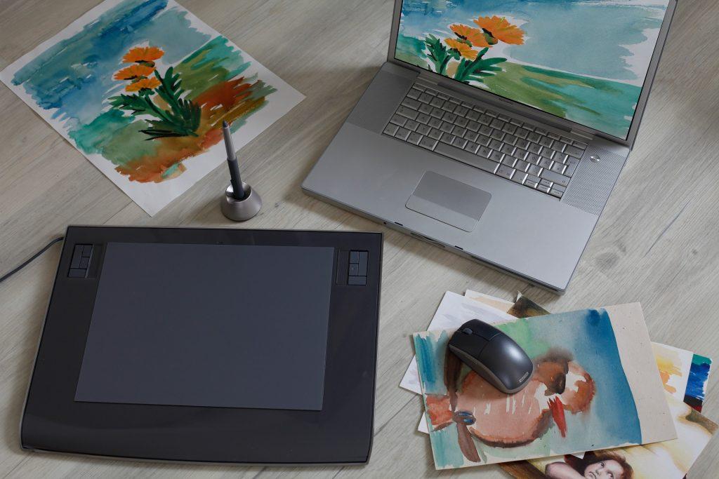 Imagem de uma mesa digitalizadora ao lado de um notebook.