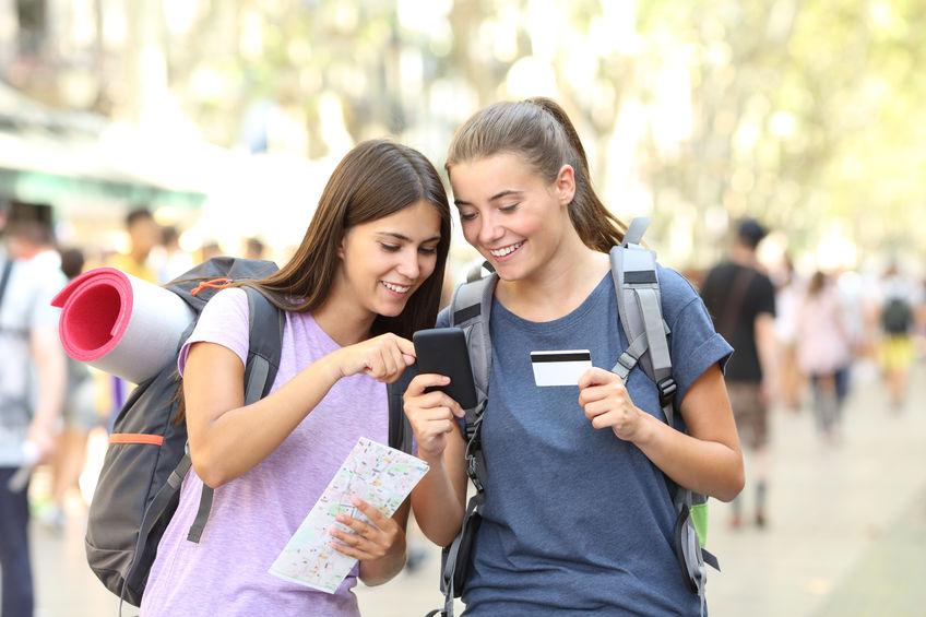 Amigas consultando algo no celular enquanto viajam.