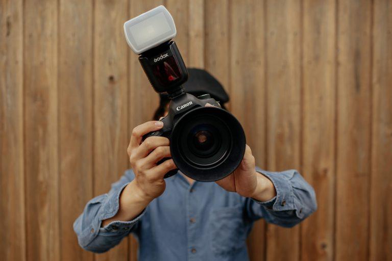 Homem com máquina fotográfica com flash Canon.
