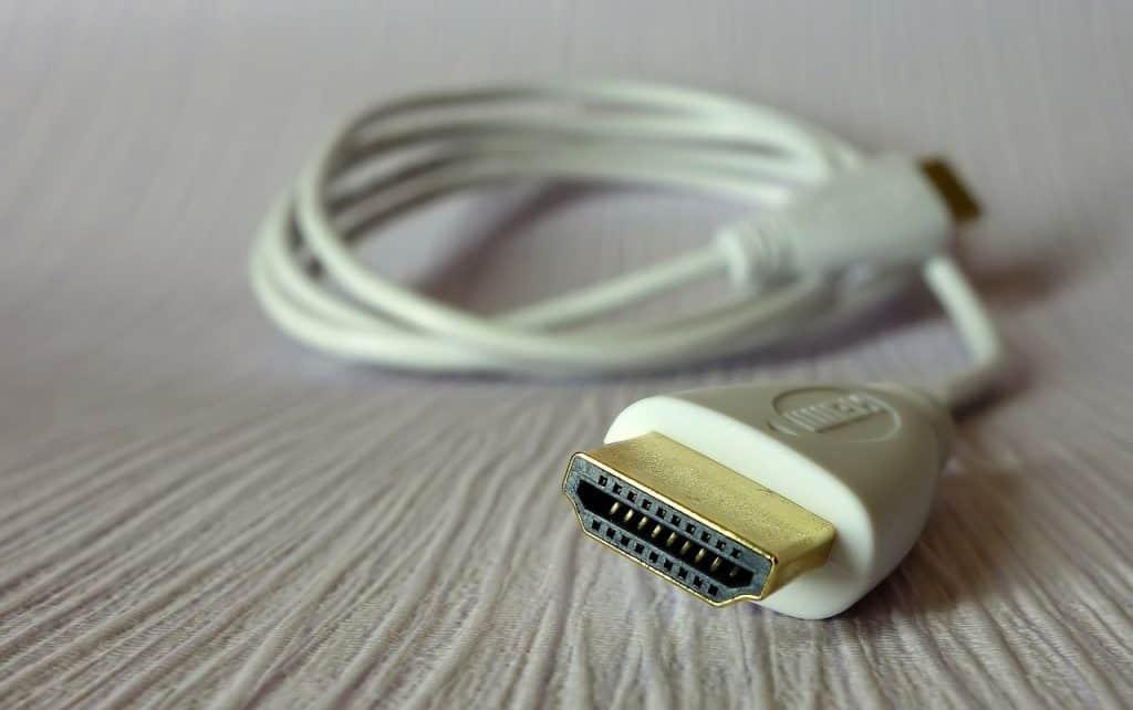 Imagem mostra um cabo HDMI branco com conector dourado.