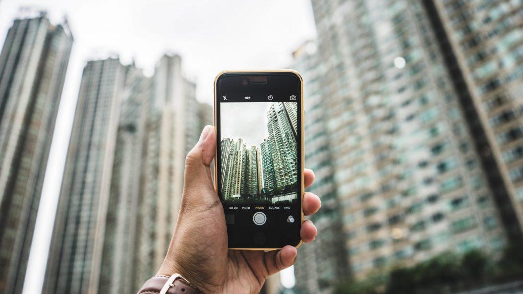 Pessoa fotografando prédios de cidade grande com o celular.