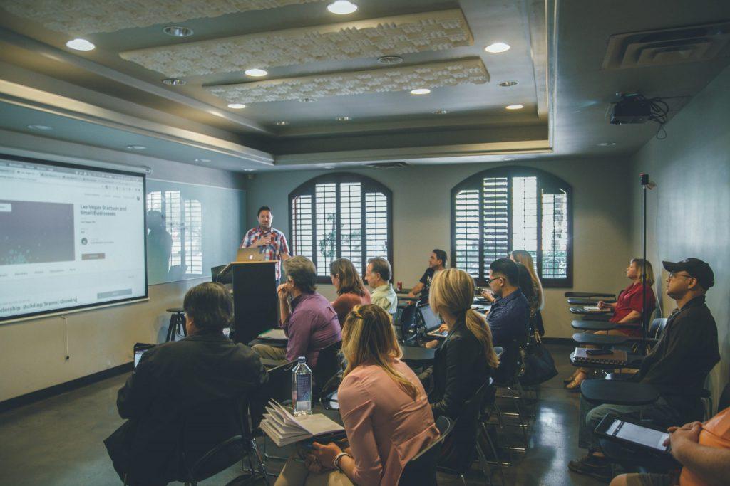Homem dando aula com projetor e alunos sentados.