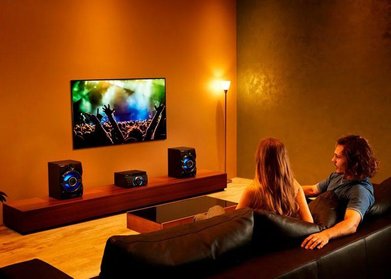 Casal sentando em sofá assistindo a um show com TV conectada em um mini system Sony.