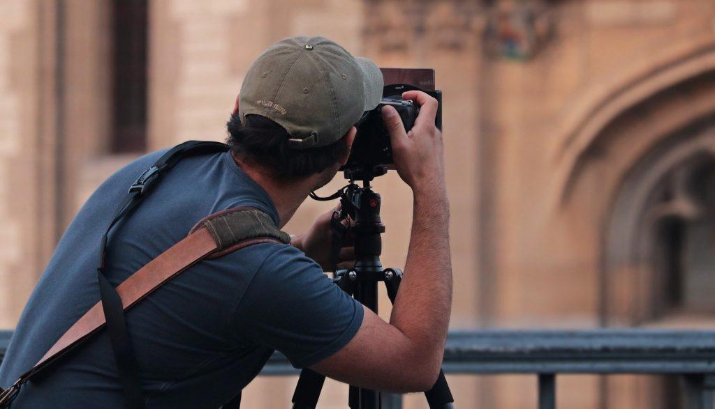 Homem fotografando prédio usando uma câmera profissional posicionada em um tripé.