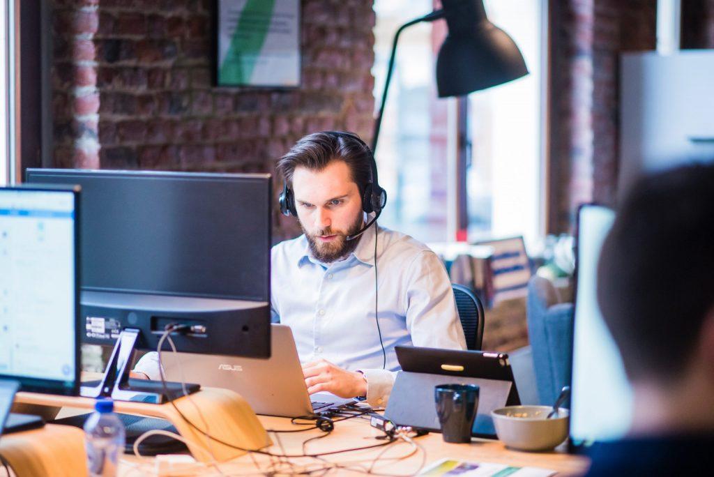Imagem mostra um homem sentado numa mesa de um escritório. Ele usa um headphone e olha para a tela de um notebook, que também está conectado a um monitor.