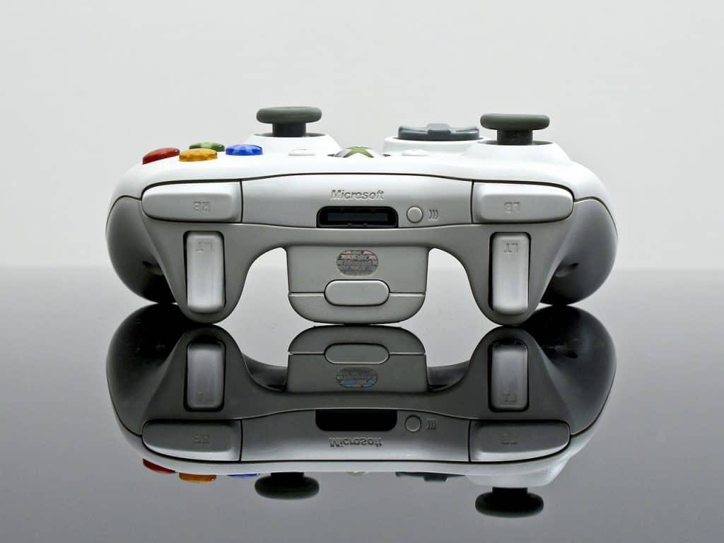 Imagem de controle branco do Xbox com reflexo na bancada.