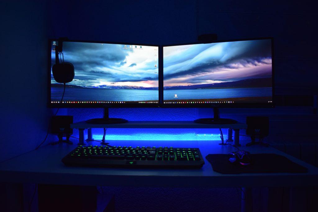 Imagem de setup gamer com dois monitores e teclado Razer