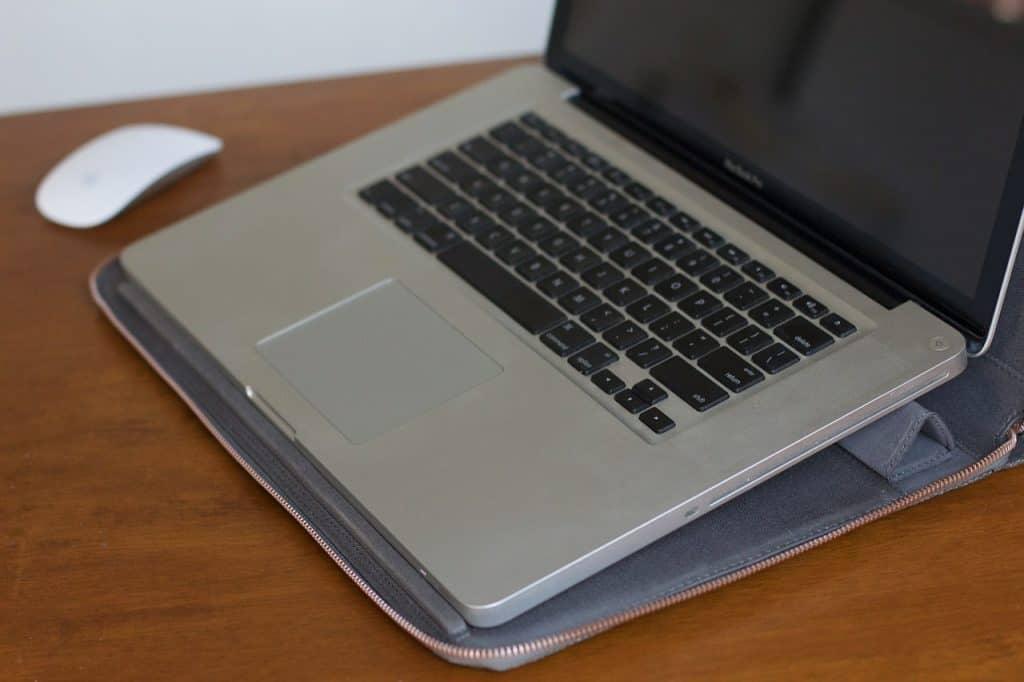 Um Macbook aberto em cima de uma capa aberta, ambos estão na parte superior de uma mesa de madeira. Há um mouse próximo ao aparelho.