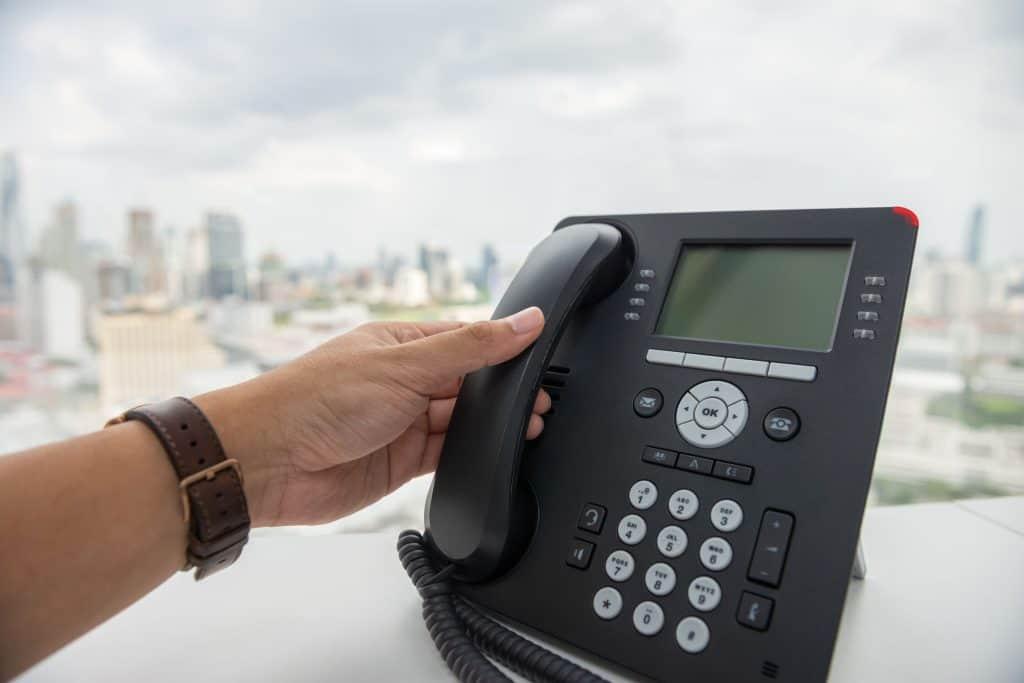 Na foto a mão de um homem pegando um telefone em cima de uma mesa.