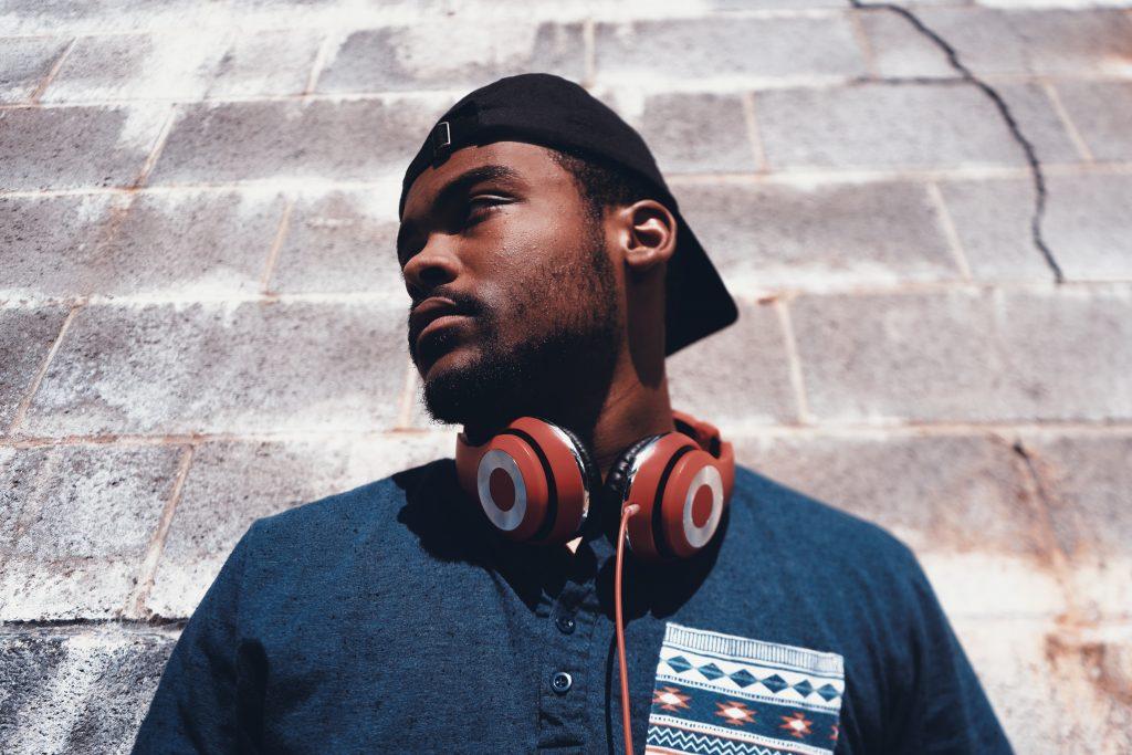 Imagem mostra homem, usando boné para trás, camisa e headphones pendurados no pescoço, apoiado num muro de concreto .