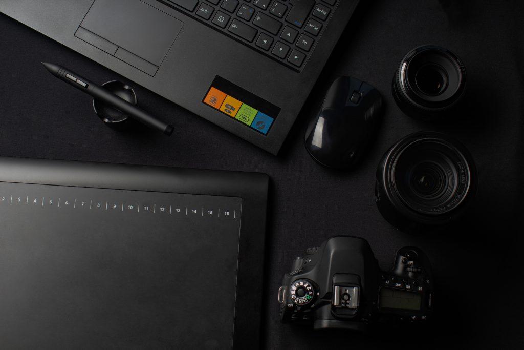 Imagem mostra um pequeno mouse sem fio ao centro de uma composição com um notebook, uma câmera, as lentes da câmera e um notepad.