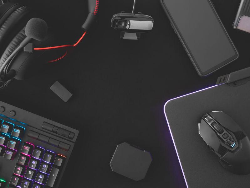 Imagem mostra uma mesa repleta de gadgets e acessórios gamer, como mouse, teclado, celular, headset e webcam.