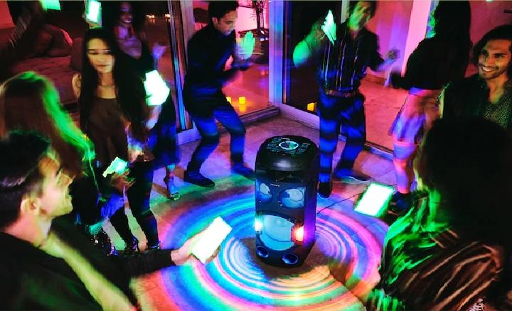 Na foto diversas pessoas dançando e uma caixa de som no meio.