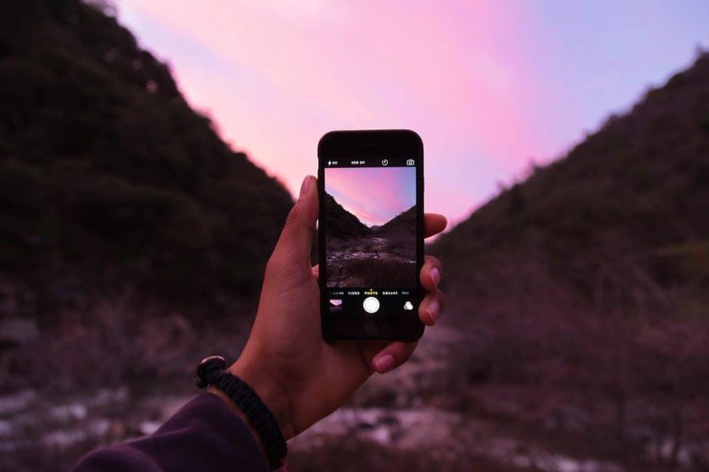 Na foto um homem segurando um iPhone com a câmera ligada mostrando uma paisagem.
