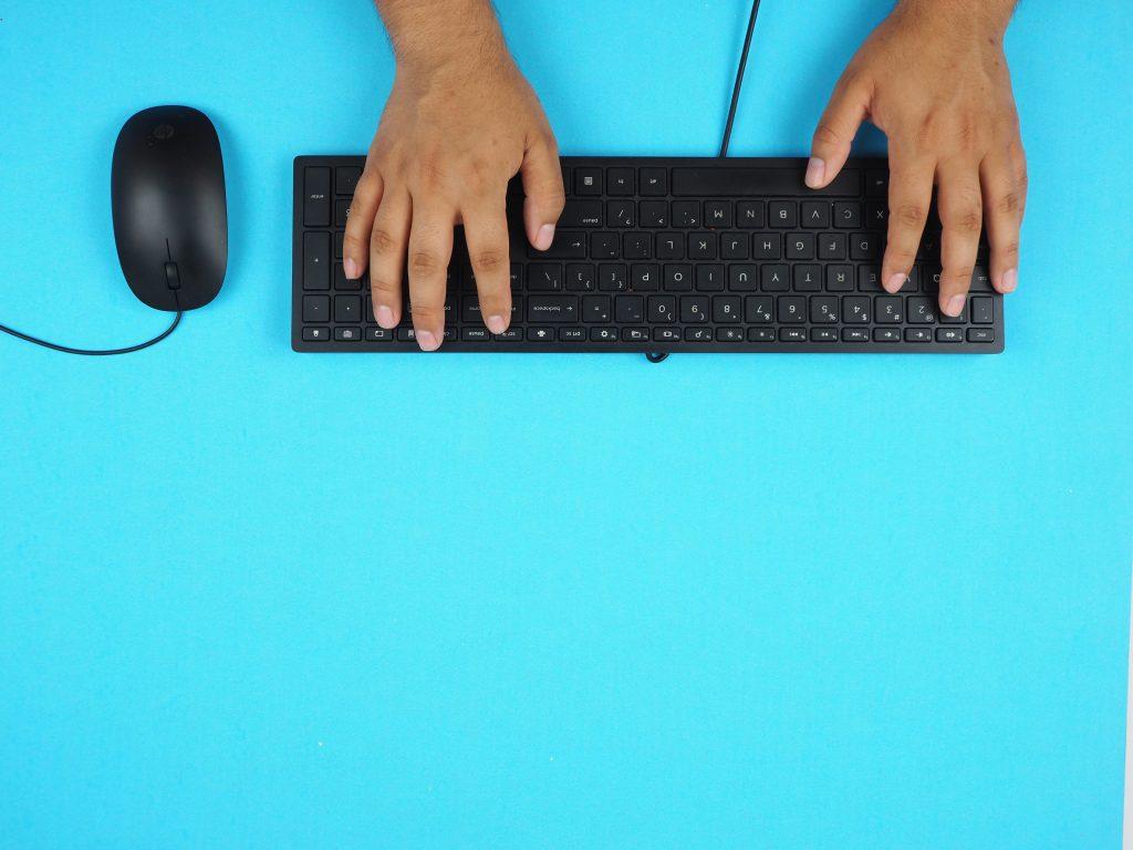 """Imagem está de """"ponta cabeça"""", com duas mãos usando um teclado, com fio, e com um mouse, também com fio, ao lado."""