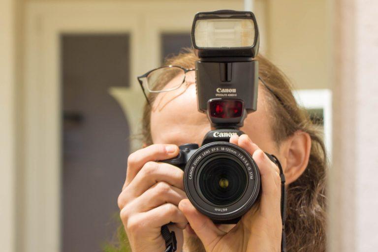 Pessoa usando câmera fotográfica com flash Canon.