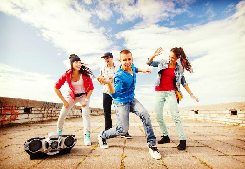 Imagem mostra um grupo de jovens num terraço, dançando ao som de um rádio portátil, que fica apoiado no chão.