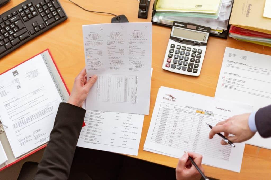 Na foto uma mesa repleta de papéis e as mãos de duas pessoas apontando para eles.