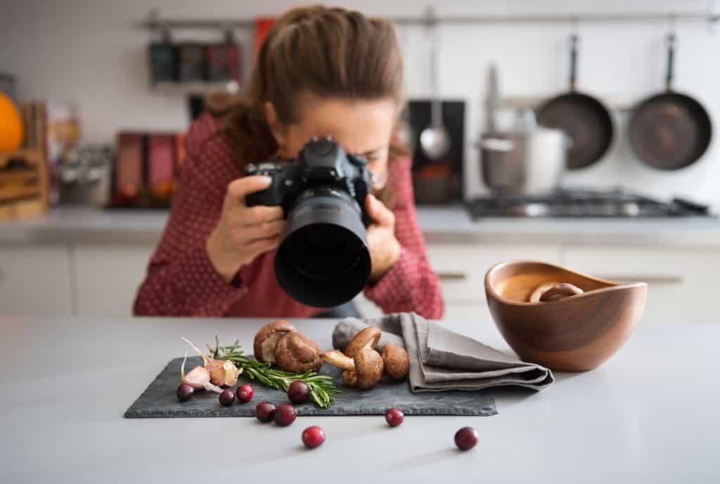 Na foto uma mulher dentro de uma cozinha com uma câmera apontada para alguns alimentos em cima de uma bancada.