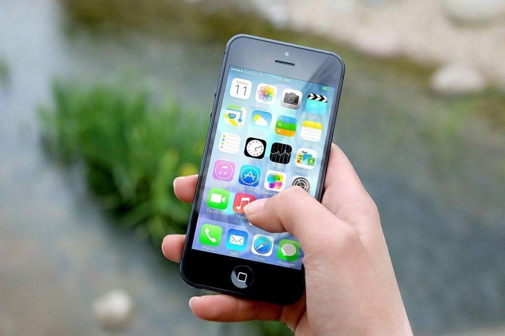 Imagem de pessoa segurando celular com destaque para os aplicativos