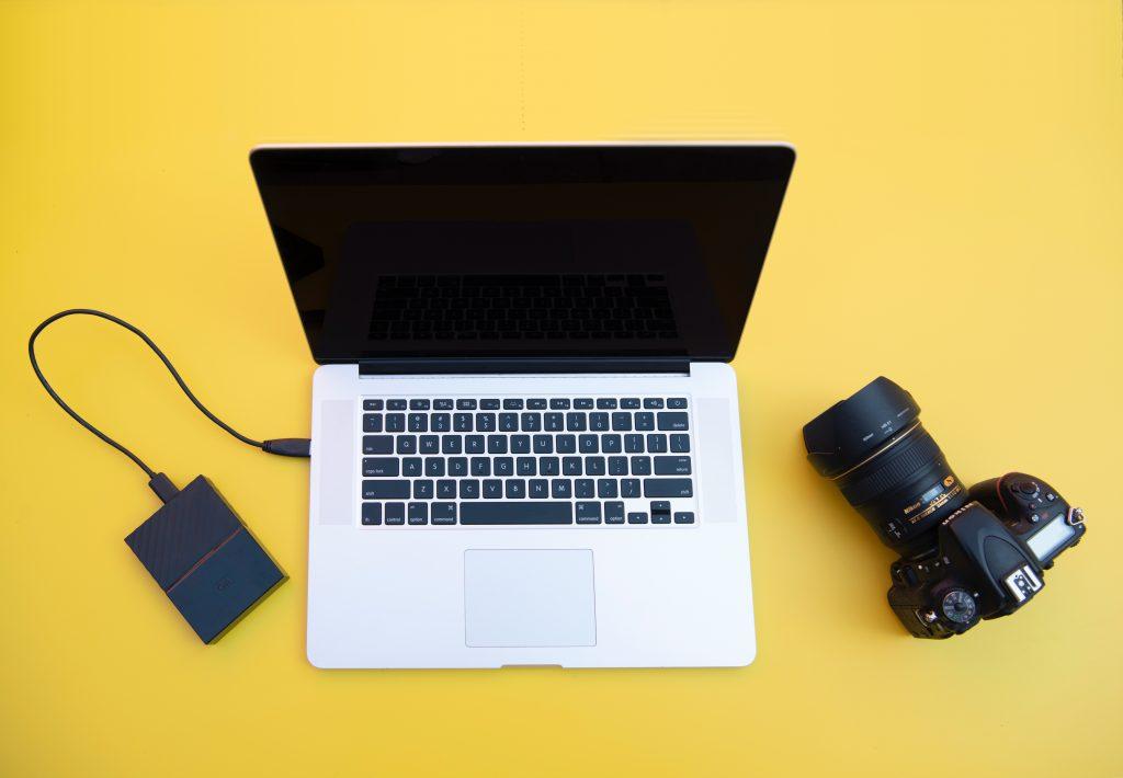 Imagem mostra uma composição, com um notebook ao centro, uma câmera fotográfica ao seu lado esquerdo e um hd externo, conectado via USB, ao seu lado direito.