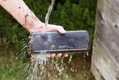 Na foto uma pessoa segurando uma caixa de som embaixo sendo molhada.