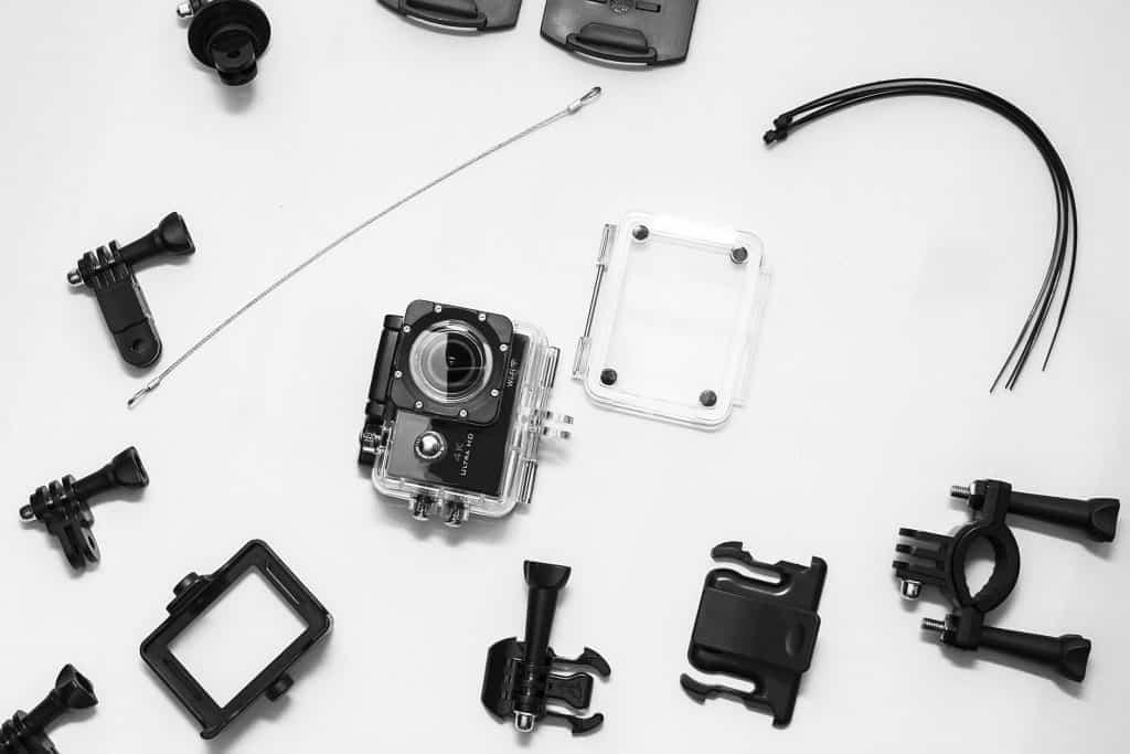 Na foto uma câmera GoPro e diversos acessórios ao seu redor.