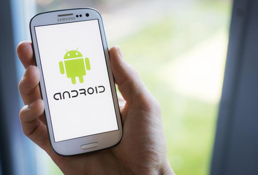 Mão masculina segurando celular Samsung com ícone do Android na tela.
