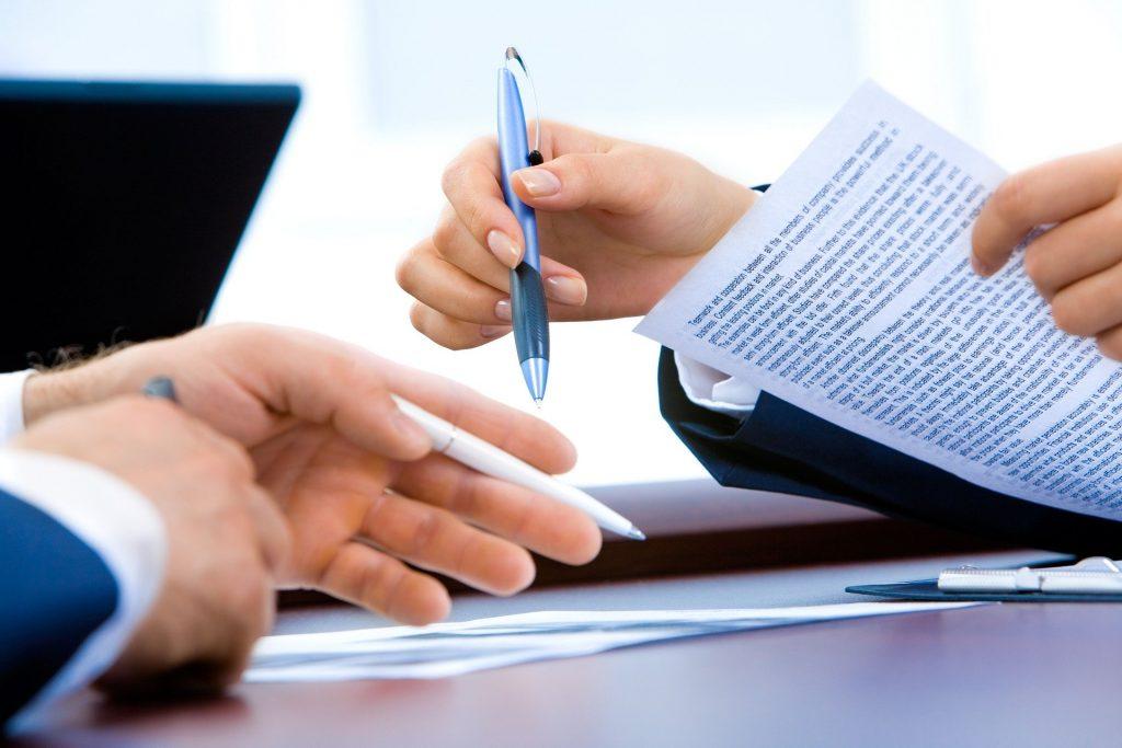 Uma mão de uma pessoa cumprimenta a mão de outra pessoa em cima de uma mesa repleta de papeis e com um notebook. Também existem duas mãos de uma outra pessoa na mesa.