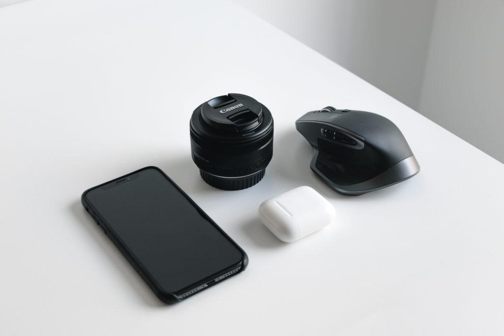 Imagem é uma composição com um smartphone, uma lente de câmera, uma caixa de fones de ouvido e um mouse sem fio dispostos lado a lado, sobre uma mesa branca.