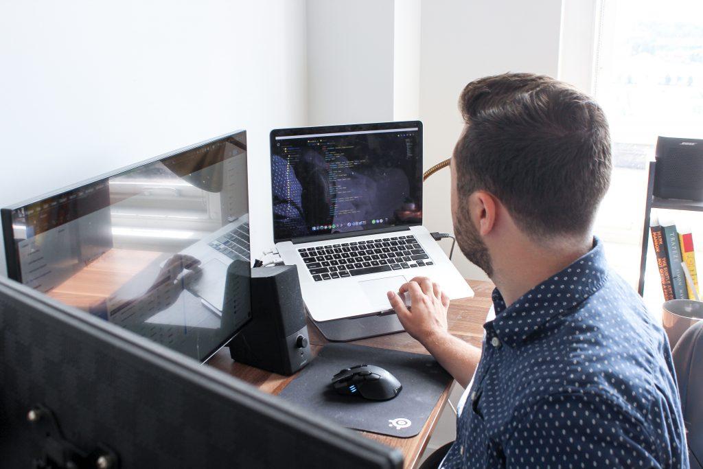 Imagem mostra um homem sentado trabalhando em um escrivaninha com um notebook ligado à outros dois monitores, a centro da escrivaninha está um mouse sem fio.